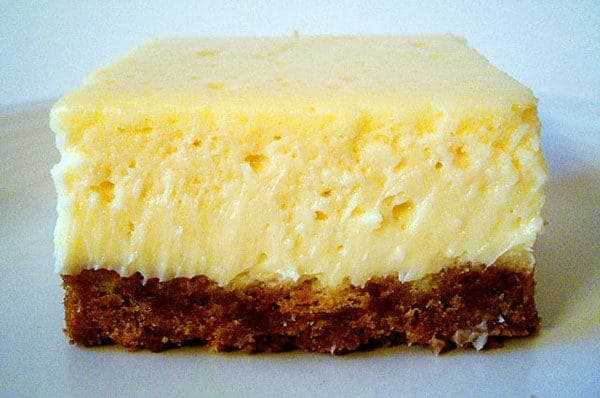cheesecake bar with a graham cracker crust on a white plate