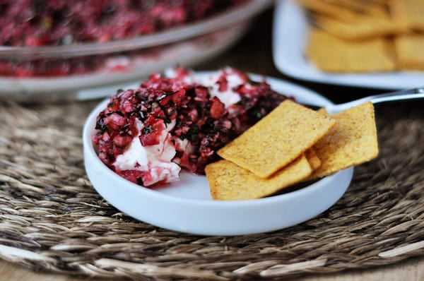 A small white dish with cream cheese and a chunky cranberry mixture on the top, and 4 crackers on the side of the dip.