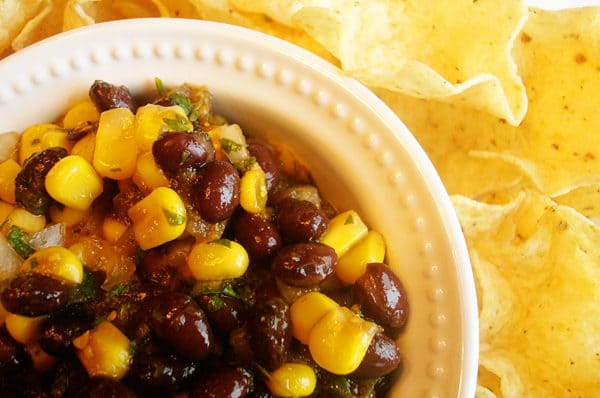 black bean and corn salsa in a white bowl next to tortilla chips