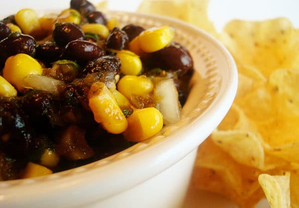 corn and black bean salsa on a plate with tortilla chips on the side