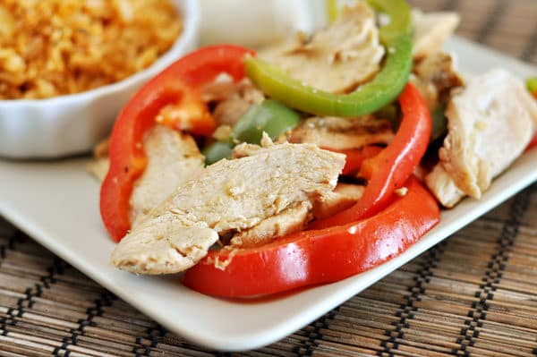 white plate of fajita chicken and peppers
