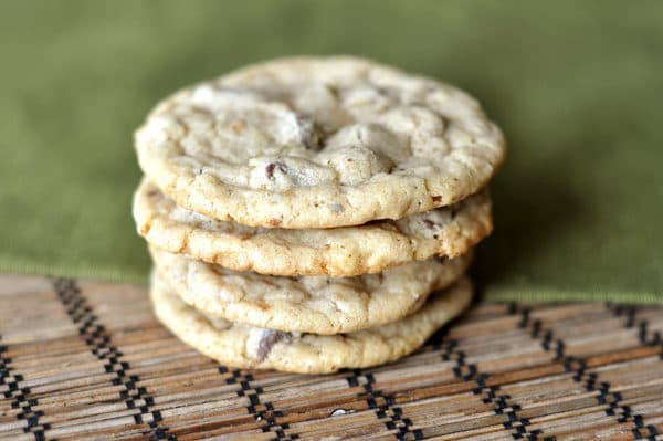 a stack of chocolate chip cookies on a mat and green napkin