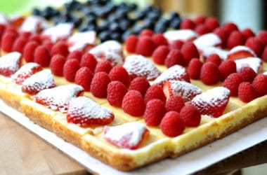 rectangular cheesecake decorated with strawberries, raspberries, and blueberries to look like an American flag
