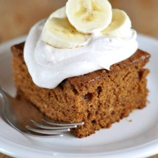 piece of gingerbread cake topped with whipped cream and sliced bananas
