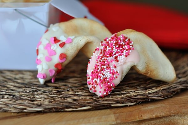 two fortune cookies half dipped in Valentine's sprinkles in front of a white container