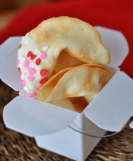 a white paper container full of cooked homemade fortune cookies