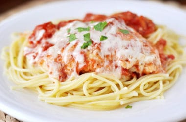 chicken parmesan with melted cheese over a bed of cooked noodles on a white plate