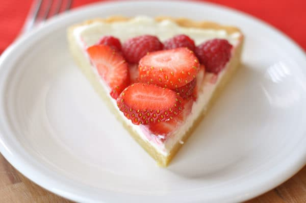 a triangle slice of fruit pizza on a white plate