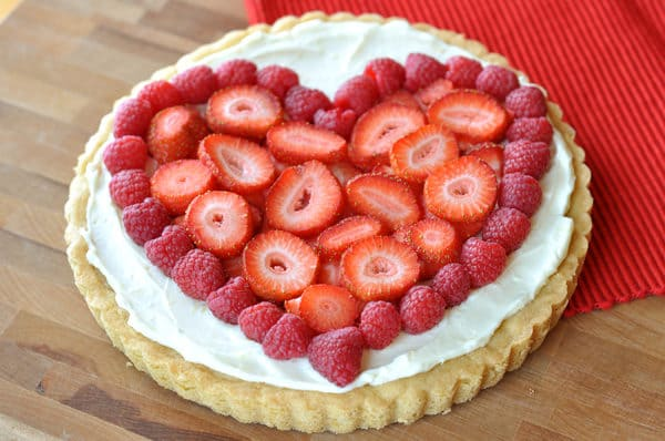 a sugar cookie crust with vanilla frosting and strawberries and raspberries on the top in the shape of a heart