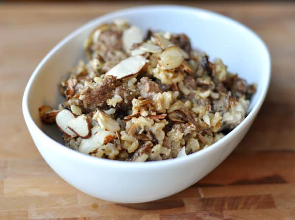 oval white bowl with cooked wild rice topped with sliced almonds