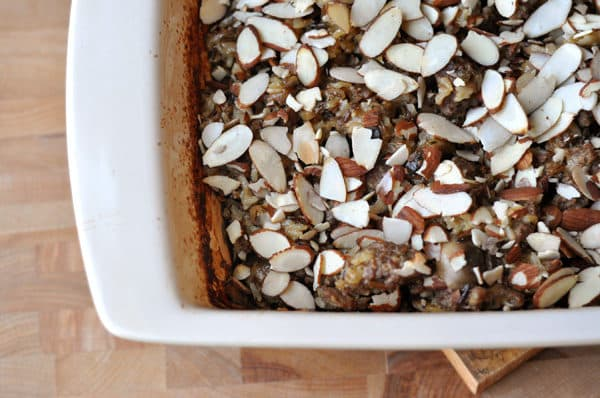 white casserole dish full of a wild rice mix and topped with sliced almonds