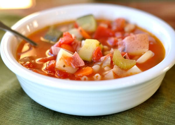 white bowl with red minestrone soup filled with vegetables and pasta