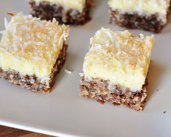 top view of coconut-topped cream cheese haystack squares on a white platter