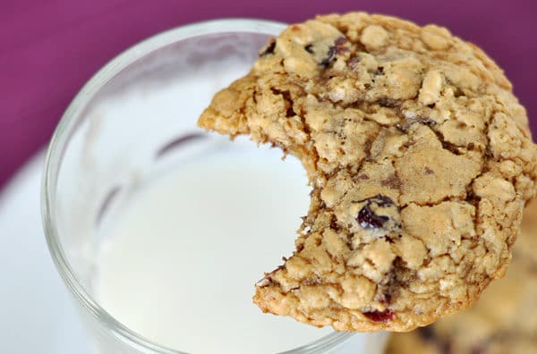 an oatmeal cookie with a bite taken out over a glass cup of milk