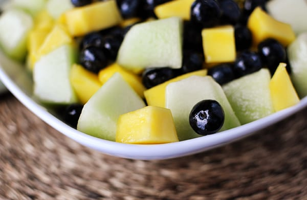 white bowl with a closeup view of a honeydew, mango, and blueberry salad