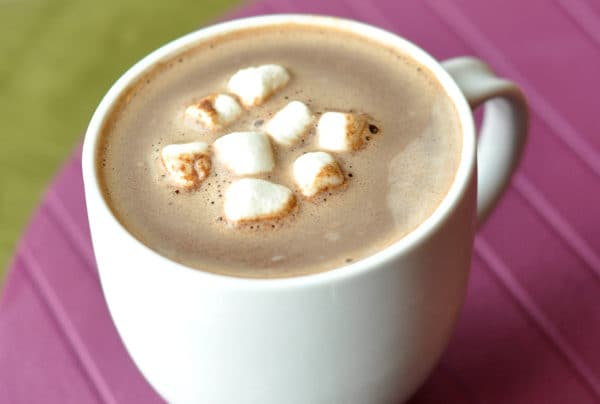 white mug filled with hot chocolate with marshmallows floating on top