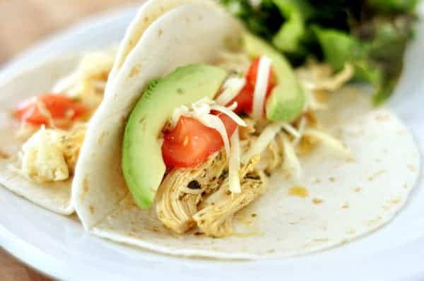 two chicken tacos with avocado slices and tomatoes