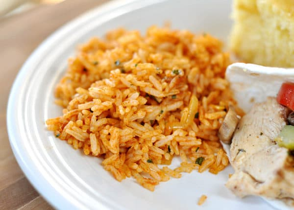 a white plate with a scoop of Mexican rice next to a chicken fajita and slice of cornbread