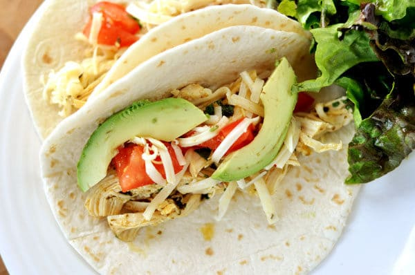 two soft shell chicken tacos with avocado and tomato on a white plate
