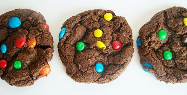 three chocolate m&m cookies lined up in a row