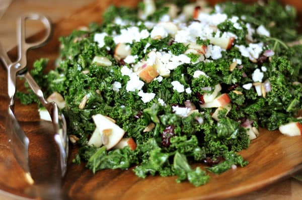 a kale and craisin salad with feta cheese and diced apples in a wooden salad bowl