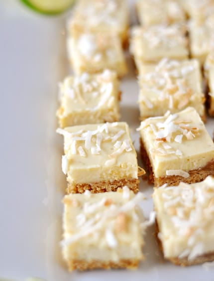 a white platter with small squares of key lime bars topped with toasted coconut