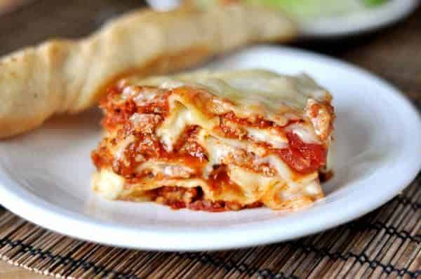 A big piece of meaty, saucy, cheesy lasagna sitting on a white plate with a breadstick laying next to it.