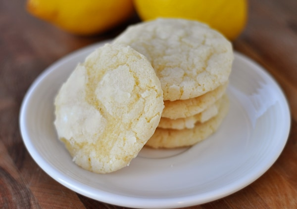 white plate with lemon crinkle cookies stacked on top of each other and one leaning on the stack