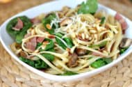 white bowl with cooked linguine, bacon, pine nuts and spinach