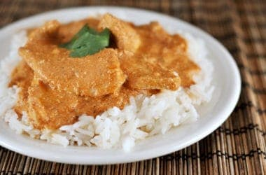 white rice with chicken and orange tikka sauce on top on a white plate