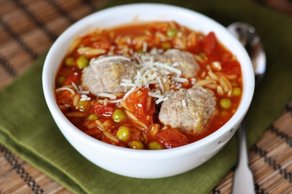 a white bowl full of pea and orzo soup with three meatballs nestled in the middle