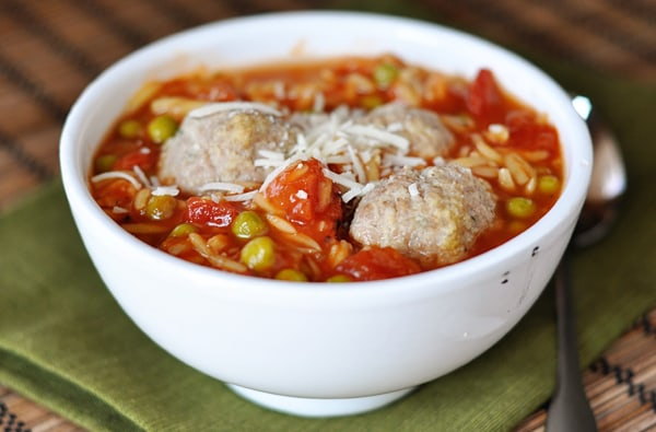 side view of a white bowl full of orzo and meatball soup