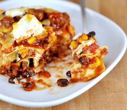 white plate with red sauce mexican lasagna filled with beef, black beans, and corn
