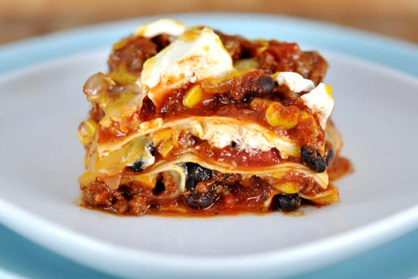 white plate with a piece of mexican lasagna layered with noodles, corn, black beans, and cheese