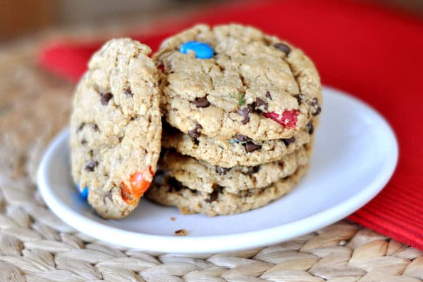 A stack of M&M chocolate chip oat cookies on a white plate.