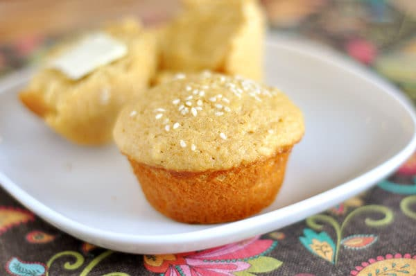 a sesame seed topped muffin in front of a muffin split in half on a white plate