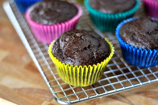 a cooling rack with chocolate muffins in colorful muffin liners on it