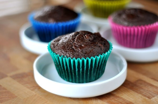 chocolate muffins in colorful liners on small white plates