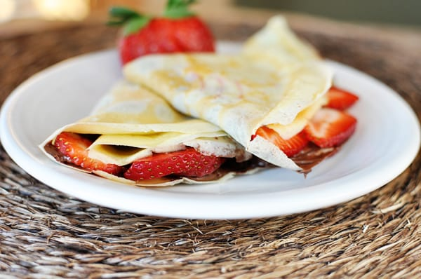 white plate with two strawberry and Nutella stuffed crepes