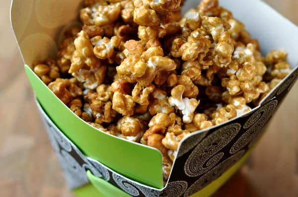 a decorative green container filled with toffee popcorn