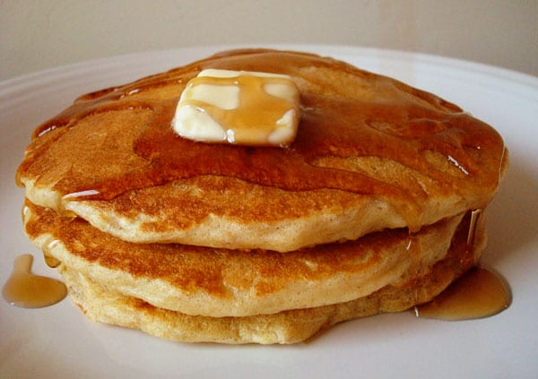 pancakes in a stack with syrup and a pat of butter on top