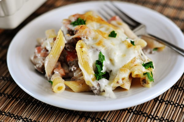 white plate with baked greek pastitio pasta, topped with melted cheese