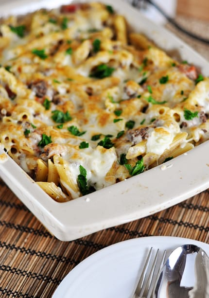 white casserole dish with a baked, cheese-topped, pastitsio Greek pasta