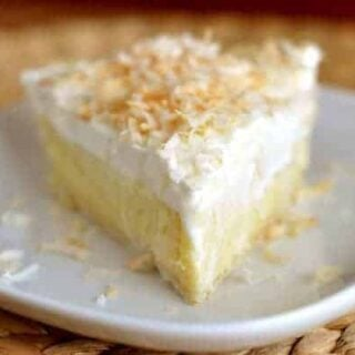 slice of coconut cream pie topped with whipped cream and toasted coconut on a white plate