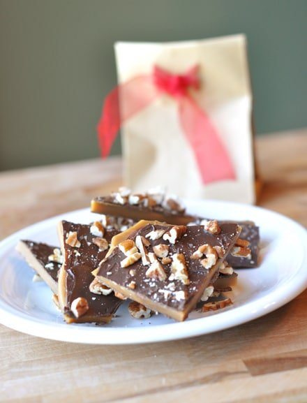 white plate of pieces of toffee buttercrunch with a paper sack and red ribbon behind it
