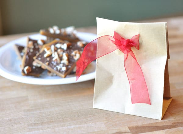 paper sack with a red ribbon next to a plate of pecan buttercrunch toffee