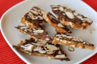pieces of almond roca stacked on their sides on a white plate