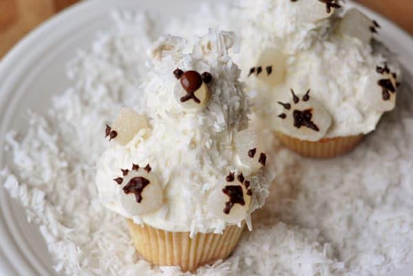 cupcakes decorated like a polar bear on a plate with shredded coconut
