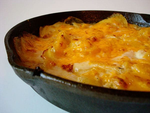 cast iron skillet with scalloped potato and melted cheese