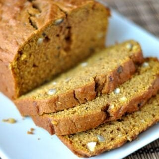 a loaf of pumpkin hazelnut bread with some slices cut on a white rectangular platter